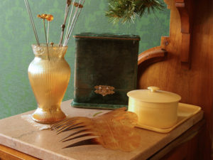 Illustrration of the type of objects found in the Museum collection. Features opaque glass vase with multiple hat pins sticking out of it, a green velvet box with gold clasp, a cream colored melamine jar with lid, and a decorative hair comb on a beige marble surface.