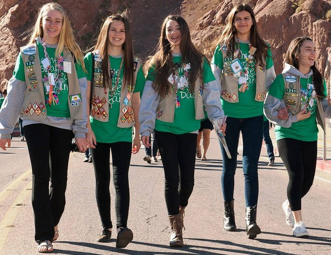 Image of five girls wearing green shirts and tan vests covered in patches