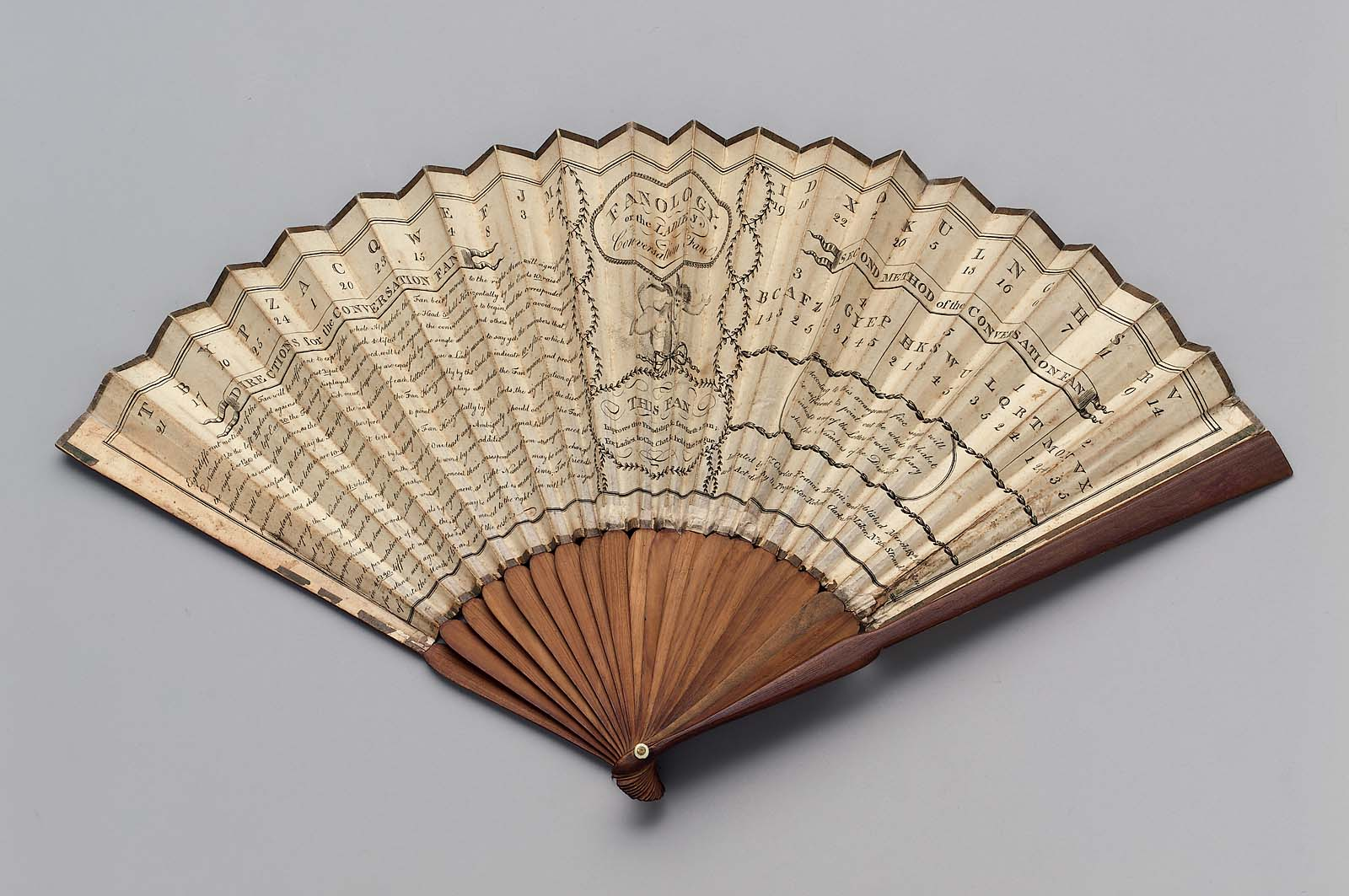 Wooden and paper fan splayed open on white background