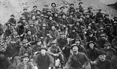 Black and white photo of approximately 60 men sitting on a dirt hillside.