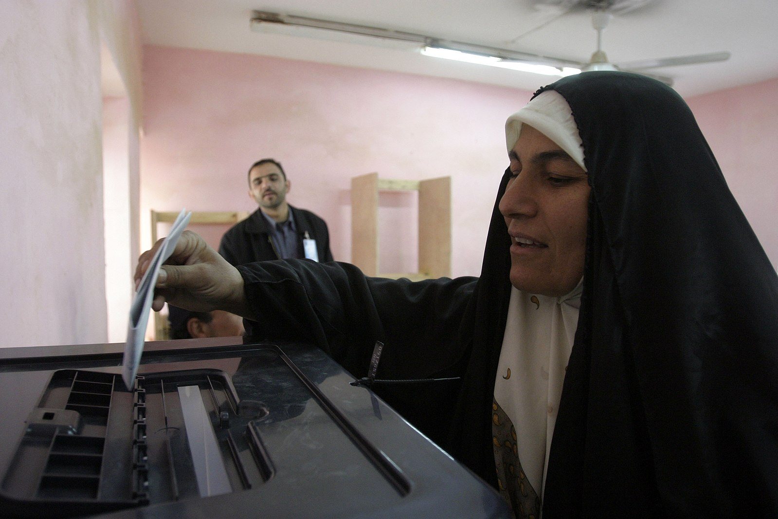 A woman drops a ballot into a ballot box