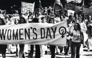 """Women marching holding a white banner that says """"Women's Day"""" and has the female symbol after it"""