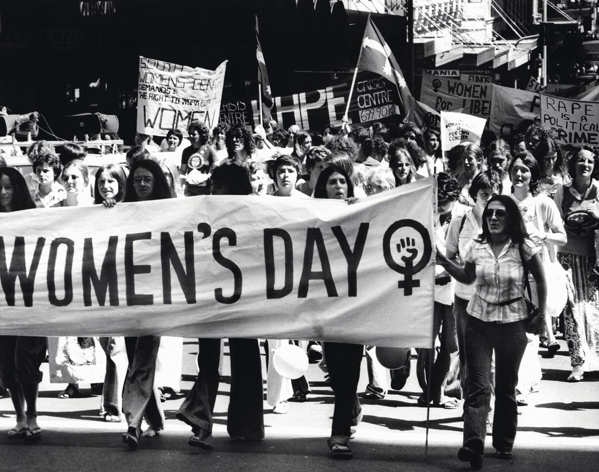 "Women marching holding a white banner that says ""Women's Day"" and has the female symbol after it"