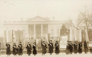 A group of women stand in front of the White House protesting, circa 1917