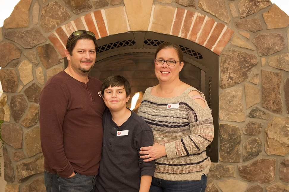 Bill, Adam, and Carrie stand in front of a fireplace
