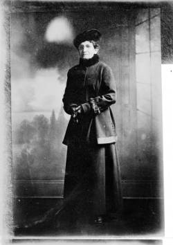 Standing portrait of women's suffragist Minnie Reynolds Scalabrino in Denver, Colorado; she wears a wool coat with a fur collar and cuffs, gloves, and a hat.