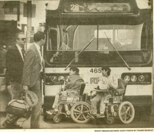 Black and white image from a newspaper. Two protesters in wheelchairs block the front of a RTD bus. Two men in suits look on as they walk in front of the bus.