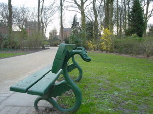 A green bench with two wooden planks sits along a park path in Belgium. The legs/back of the bench are shaped like dragons.