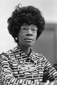 Black & white image of Shirley Chisholm looking ahead and slightly to the right of the viewer. Link to event registration.