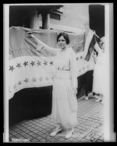 Alice Paul, full-length portrait, standing, facing left, raising glass with right hand
