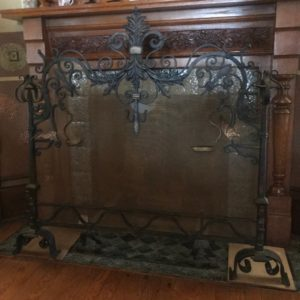Ornate iron and copper fireplace screen.