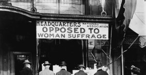 "Sign over a storefront that reads ""Headquarters National Association Opposed to Woman Suffrage"" with four men appearing to read papers while facing the storefront. A woman looks back at them as she walks by. Circa 1911."