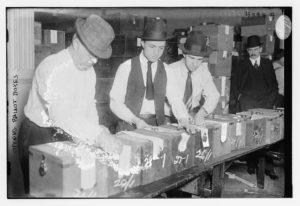 Black and white image of three men opening sealed ballot boxes. Used as link for registration.