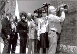 Board members of Historic Denver placing a landmark plaque on a building. Link to event registration.